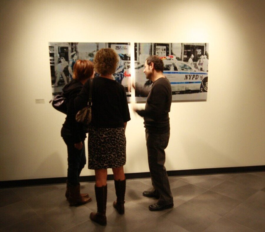 three people commenting on a painting in a gallery