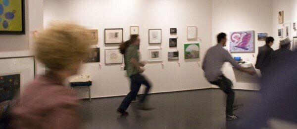people dashing about a gallery