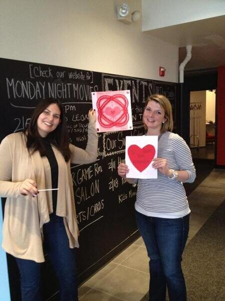two women holding up valentines day artwork