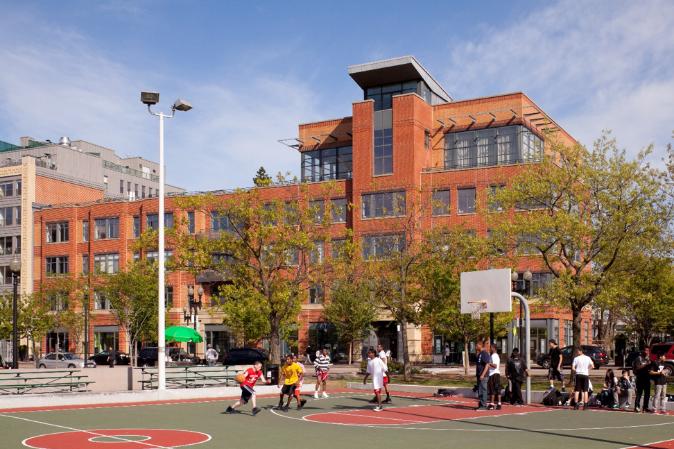 View of laconia lofts from peters park with kids playing basketball