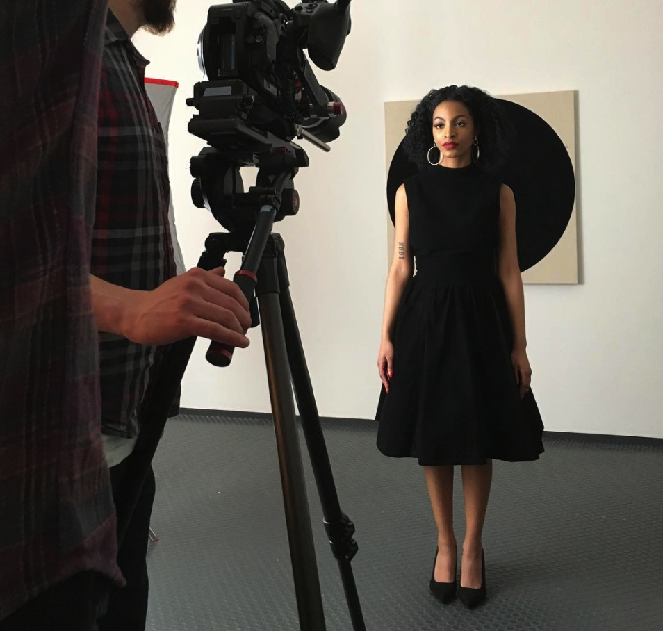 Model posing for a camera in a gallery